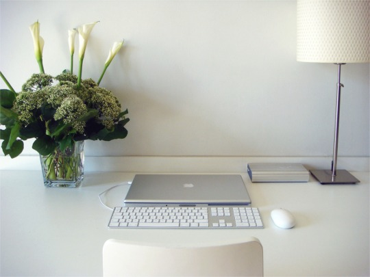A minimalist clear white desk with laptop, flowers and stylish desk lamp