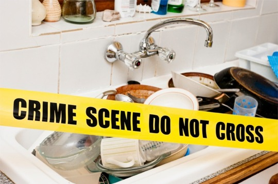 A sink full of dirty dishes with yellow warning sign across
