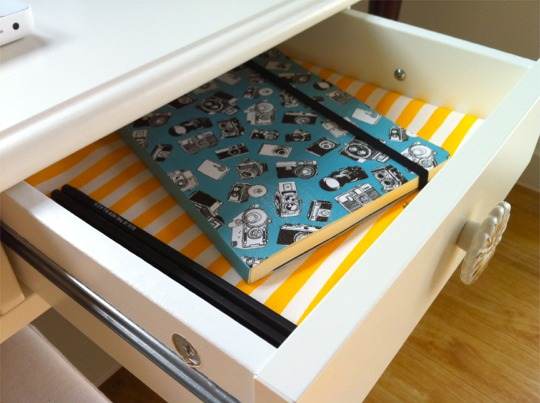 Desk drawer lined with yellow and white striped paper and notebook with camera illustrations on cover