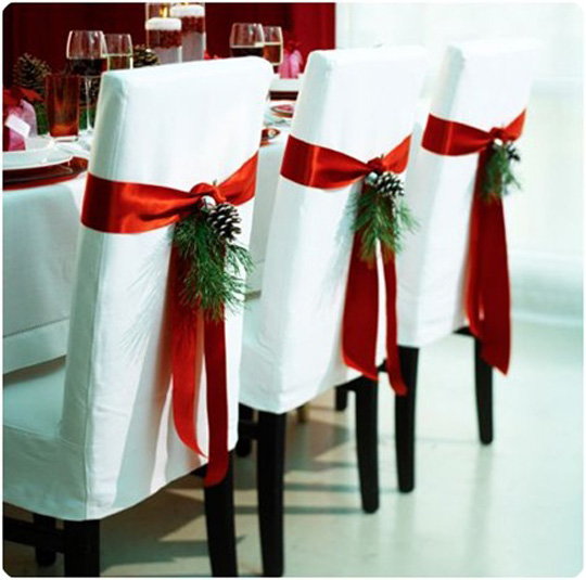 Chair decorations for Christmas place setting with red ribbons, pine cones and pine needles