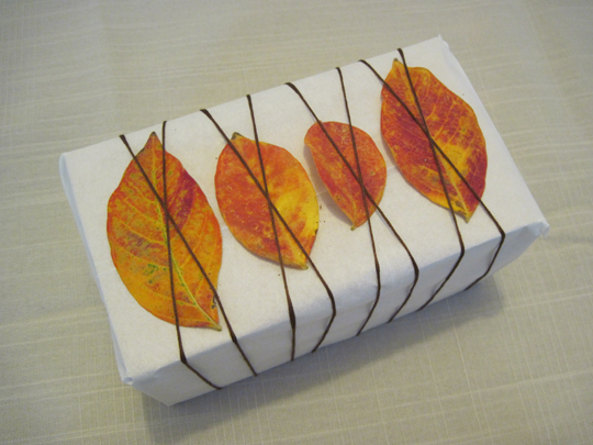 Gift wrapping using autumn leaves and twine