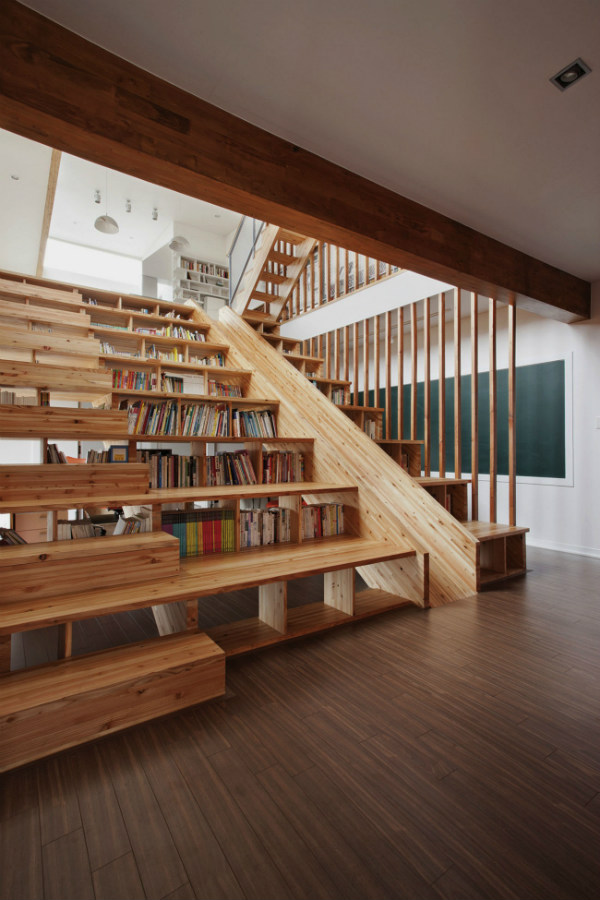 Staircase with bookshelves and a slide
