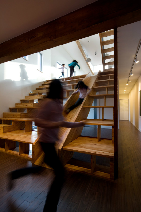 Staircase with a slide and bookshelves