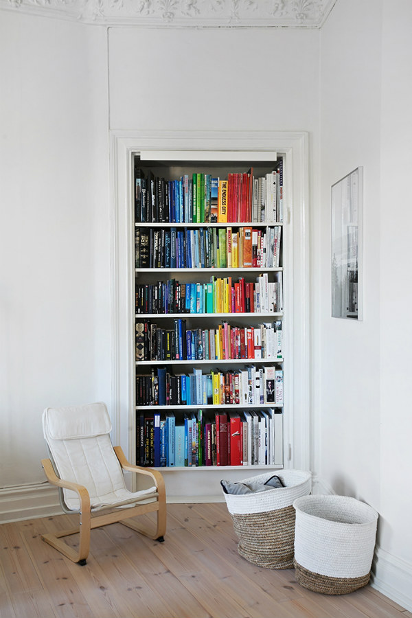 Reading corner with bookshelves and books arranged in colour