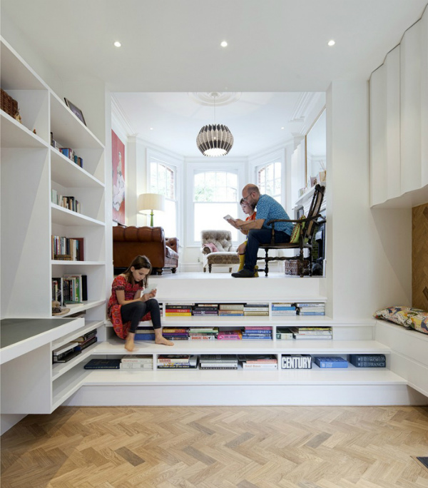 Living room with shelves for books in the risers of the stairs
