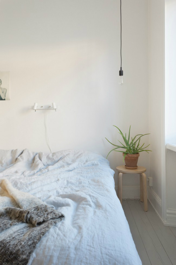 Scandinavian style bedroom with stool as a bedside table