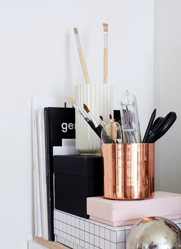 Shelf with metallic home decor accents and a storage box in pantone rose quartz