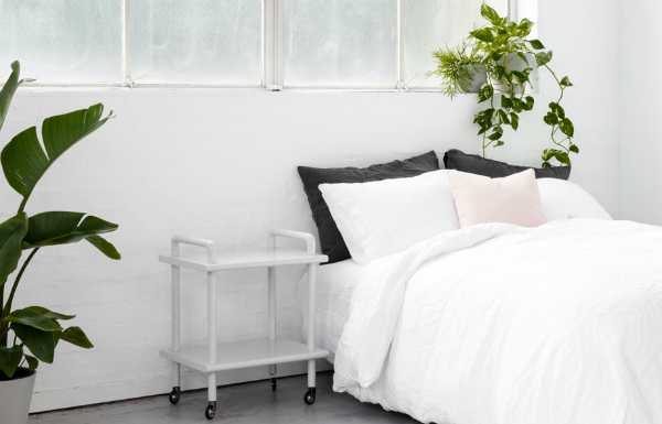 White bedroom with plants, grey and rose quartz pink accents