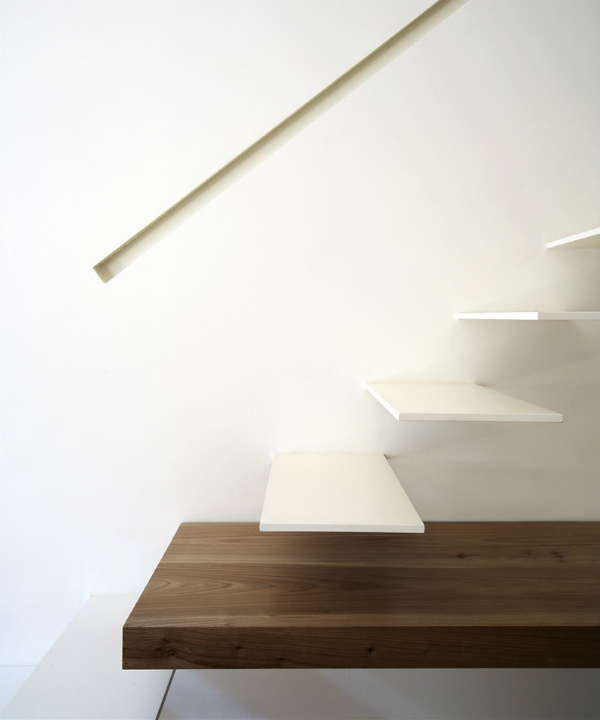 Architectural cantilevered white staircase with recessed handrail