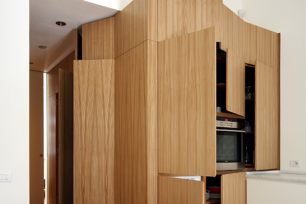 Minimalist kitchen hidden behind wood doors